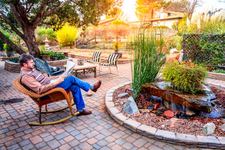 Man is reading a newspaper on a patio in a cozy garden Imagens