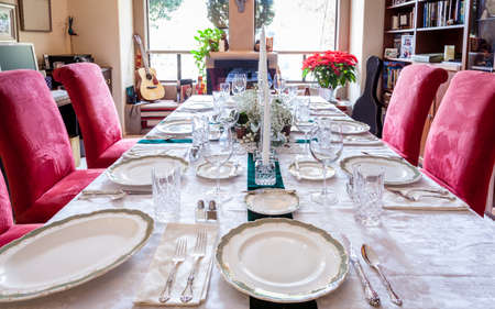 dining table and chairs: Dining table is set for a holiday dinner