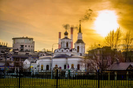 juxtaposition: Church of the Feast of the Cross at the Clean Gorge juxtaposed with smoke stacks of a power plant in Moscow, Russia Stock Photo