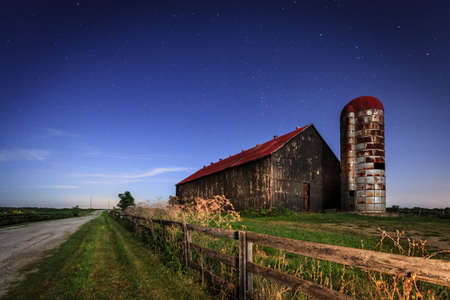 Scenic nighttime image of an old farm barn and a country road in moonlight Stockfoto