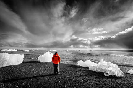 Tourist standing among ice pieces on a beach in southern Iceland. Selective color image