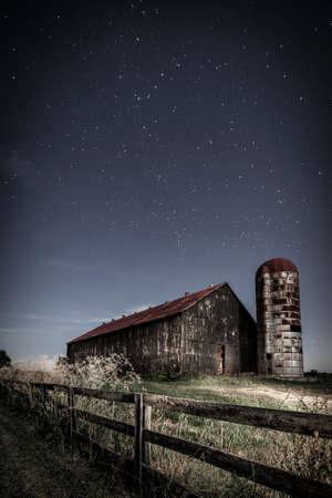 luz de luna: Imagen nocturna escénica de un viejo granero de la granja y de un camino rural en el claro de luna Foto de archivo