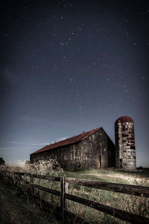barn: Scenic nighttime image of an old farm barn and a country road in moonlight Stock Photo