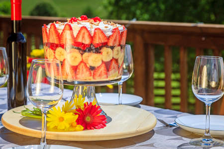 trifle: Outdoor patio table setting with trifle and wine