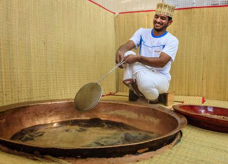 dishdasha: NIZWA, OMAN, MAY 27, 2016: factory worker skims foam from sugar syrup as part of process of making traditional Omani halwa