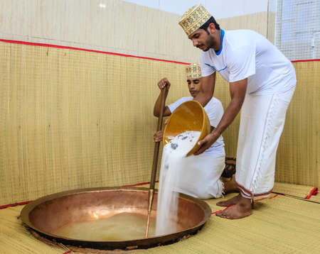 stirring: NIZWA, OMAN, MAY 27, 2016: factory worker pours sugar into a copper kettle for making of traditional Omani halwa Editorial
