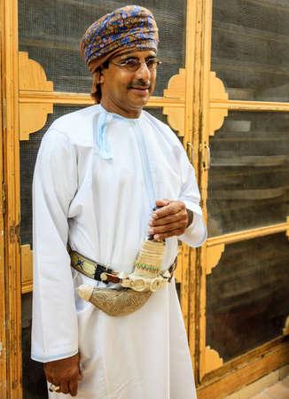 dishdasha: NIZWA, OMAN, MAY 27, 2016: An Omani man in a traditional outfit wearing khanjar - a traditional dagger on a belt