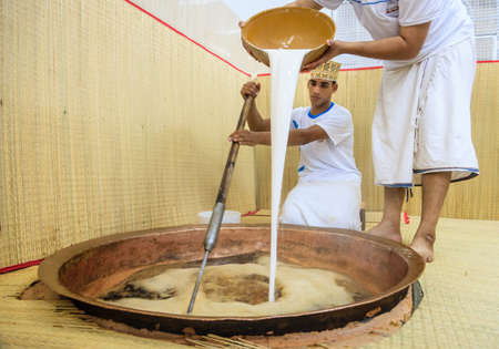 dishdasha: NIZWA, OMAN, MAY 27, 2016: factory worker pours tapioca starch into a copper kettle for making of traditional Omani halwa