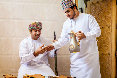 dishdasha: NIZWA, OMAN, MAY 27, 2016: two Omani men having traditional Omani coffee