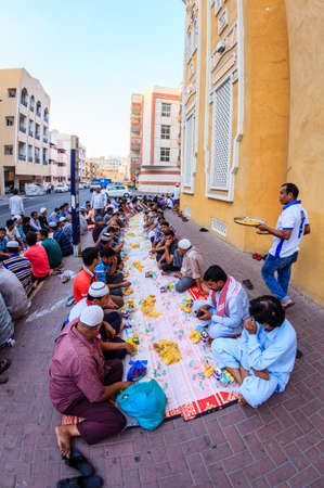 bur dubai: Dubai, June 14, 2016: men are gathered for iftar dinner near a mosque in Bur Dubai, UAE Editorial