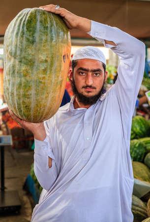 dishdasha: Dubai, June 4, 2016: a local vendor with a giant squash at the fruit and vegetable market in Dubai, UAE Editorial