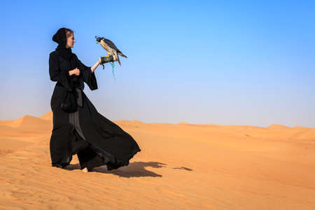 birds desert: Young woman in abaya with Peregrine Falcon in Dubai Desert Conservation Reserve, UAE Stock Photo