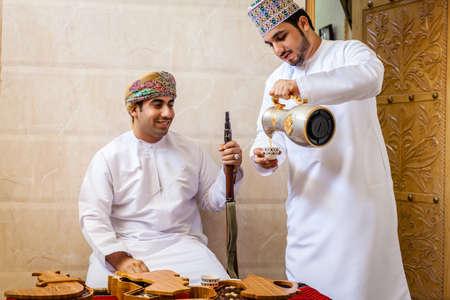 east espresso: NIZWA, OMAN, MAY 27, 2016: two Omani men having traditional Omani coffee