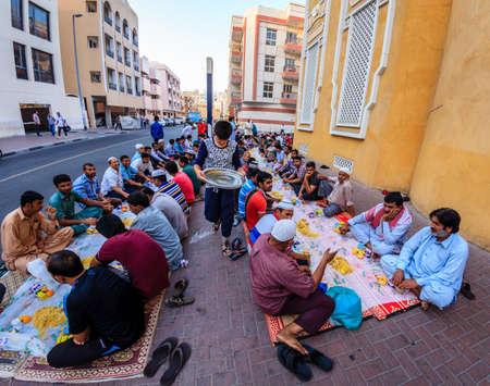 Dubai, June 14, 2016: men are gathered for iftar dinner near a mosque in Bur Dubai, UAE Editorial