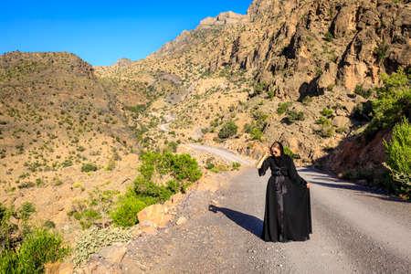 A woman in black abaya is walking on a road in Al Hajar Mountains in Oman Stock Photo