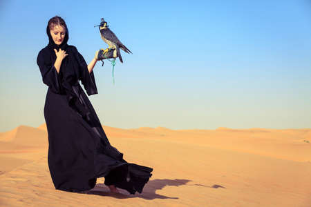 peregrine falcon: Young woman in abaya with Peregrine Falcon in Dubai Desert Conservation Reserve, UAE Stock Photo