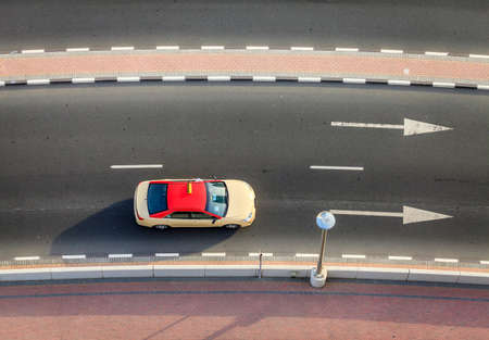 Top view of a taxi driving on a street of Dubai