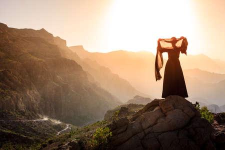 Eenzame vrouw in abaya in Al Hajar gebergte van Oman bij zonsondergang