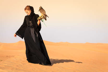 Young woman in abaya with Peregrine Falcon in Dubai Desert Conservation Reserve, UAE Stock Photo