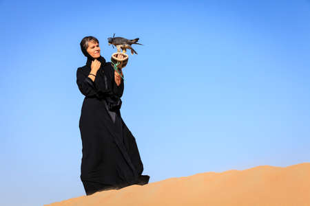 A woman in abaya with Peregrine Falcon in Dubai Desert Conservation Reserve, UAE Stock Photo