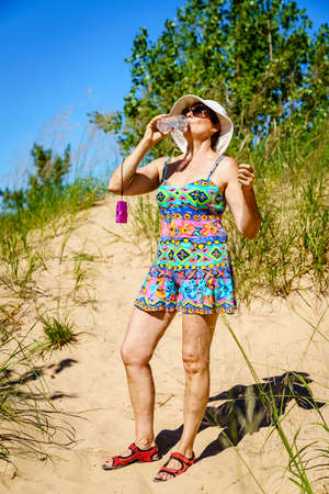 Woman is drinking water while hiking in the dunes in Northern Michigan Stock Photo