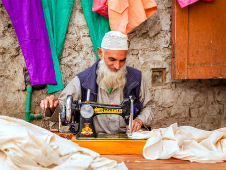 Leh, Ladakh, India, July 12, 2016: a tailor is working at his shop on a small street in Leh, India Editoriali
