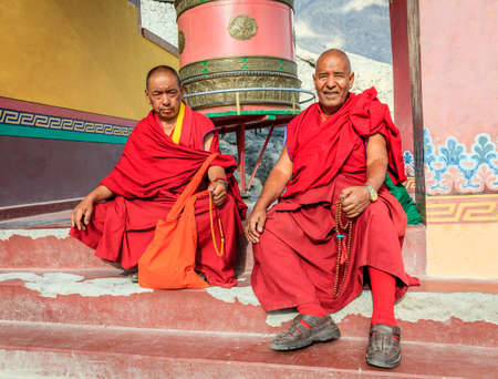 Nubra Valley, Ladakh, India, July 14, 2016: two monks siting by a praying drum in Diskit Monastery in Ladakh region of Kashmir, India