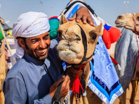 Dubai, United Arab Emirates - March 25, 2016: Camel handler with his animal at Dubai Camel Racing Club 新聞圖片