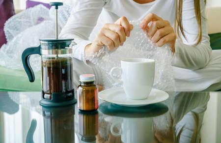 Womans hands popping bubble wrap. Stress concept