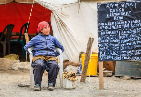 Ladakh, India, July 16, 2016: local woman sits by the menu sign of a roadside canteen in Changthang plateau Ladakh, Kashmir, India