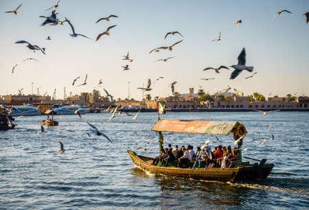 Dubai, UAE, February 5, 2016: Abra is making its way across Dubai Creek as flock of seagulls circling above