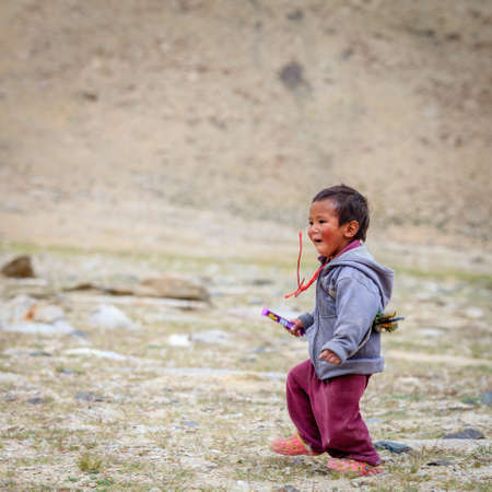 Ladakh, Kashmir, India, July 16, 2016: local boy is running in the field in the highlands of Ladakh district of Kashmir, India