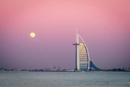 Dubai, UAE, December 13, 2016: full moon is rising over Burj Al Arab - the world's only 7-star luxury hotel