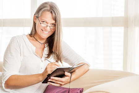 Mature woman is making notes in her diary sitting on a couch in her apartment