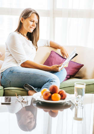 Mature woman is relaxing on a couch in her apartment with a magazine