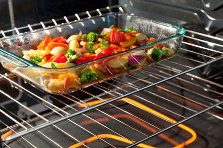 Fresh vegetables roasting in a clear dish in the oven Stock Photo