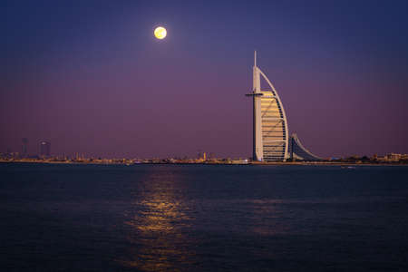 Dubai, UAE, December 13, 2016: full moon is rising over Burj Al Arab - the worlds only 7-star luxury hotel