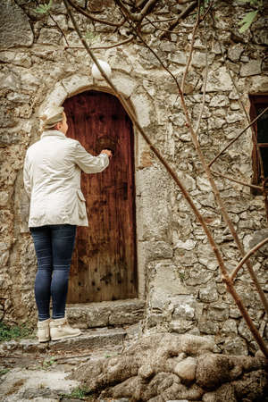 A woman knocks on the door of an old house in a Bosnian village
