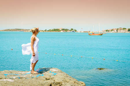 Beautiful woman is looking over coastline near Sozopol, Bulgaria Stock Photo