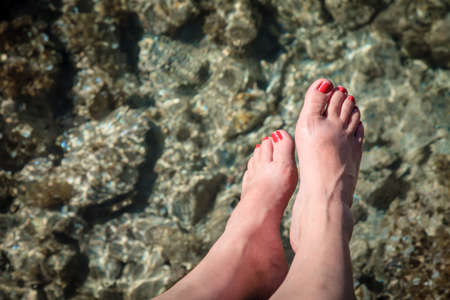 Close-up image of womans feet over clear waters in British Virgin Islands