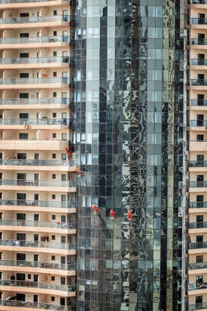 Maintenance crew is cleaning windows of a skyscraper in Dubai, UAE Stock Photo
