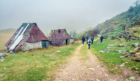 Hikers walk by dilapidated building in an old Bosnian village in the mountains