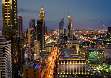 Birds eye view of Dubai Financial District skyline and rush hour traffic after sunset