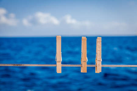 Cllose-up image of wooden cloth pins on a sailboat railing