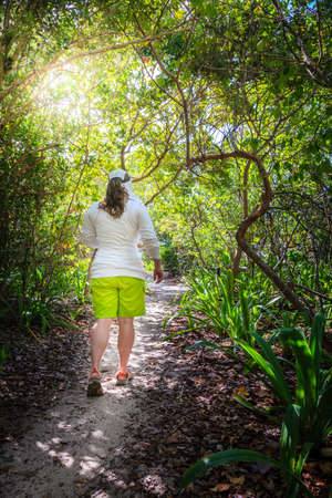 Woman is walking through a forest on a small island in the Caribbean