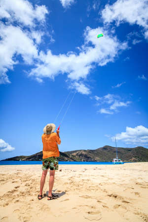 A man is flying a kite on a tropical beach in the Caribbean