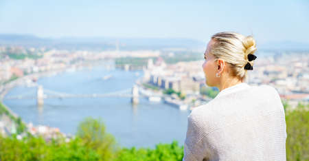 A woman tourist is enjoying view of Budapest city center and the Danube River