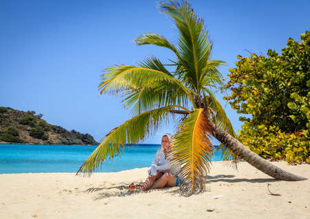 Woman is resting in shade of a palm tree on a beach in British Virgin Islands