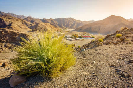 Scenic overlook of Al Hajar mountains in the emirate of Fujeirah, UAE and a village in a valley Stock Photo