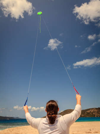 A woman is flying a kite on a tropical beach in the Caribbean Stock Photo